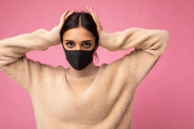 Junge frau, die eine antivirus-schutzmaske trägt, um andere vor einer corona-covid-19- und sars-cov-2-infektion einzeln auf rosafarbenem hintergrund zu schützen