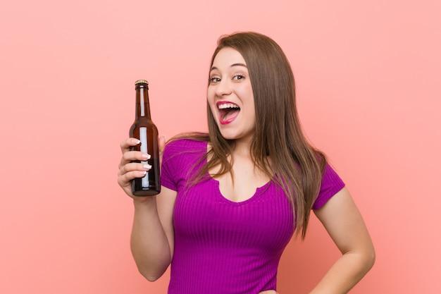 Junge frau, die eine bierflasche hält