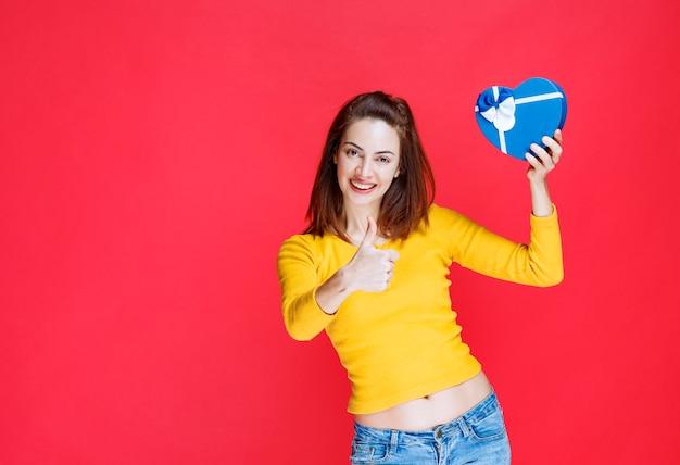 Junge frau, die eine blaue geschenkbox in herzform hält und daumen nach oben zeigt