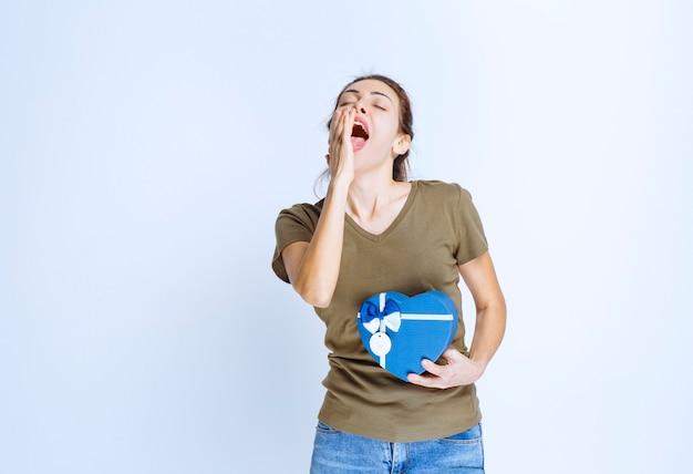Junge frau, die eine blaue geschenkbox in herzform hält und laut schreit