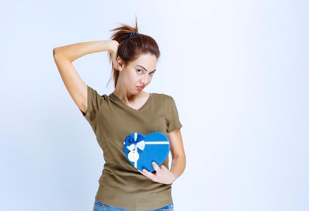 Junge frau, die eine blaue geschenkbox in hörform hält und sich zufrieden fühlt