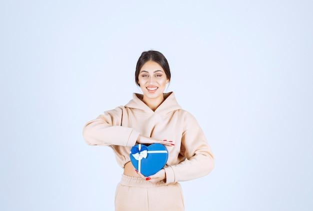 Junge frau, die eine blaue herzform-geschenkbox hält und glücklich aussieht