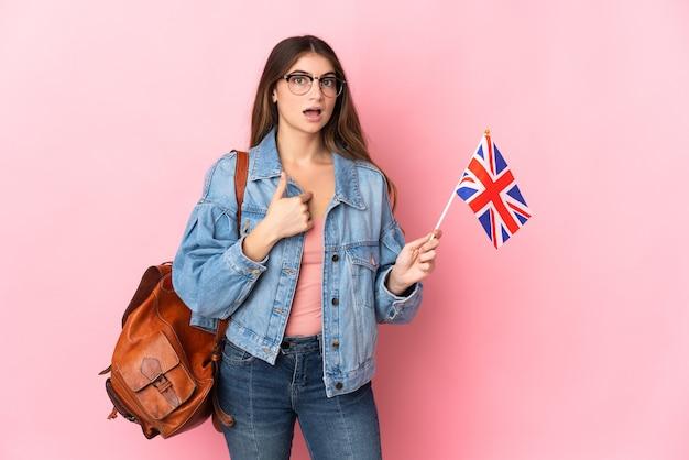Junge frau, die eine britische flagge auf rosa mit überraschendem gesichtsausdruck hält