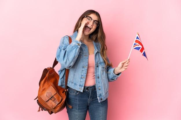 Junge frau, die eine britische flagge auf rosa schreien mit weit geöffnetem mund hält