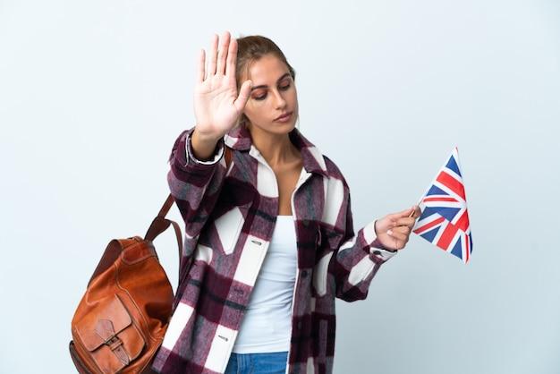Junge frau, die eine britische flagge auf weiß hält, macht stoppgeste und enttäuscht