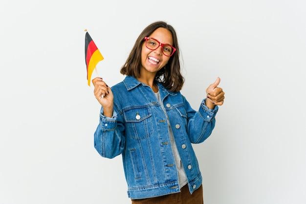 Junge frau, die eine deutsche fahne lokalisiert auf weißer wand hält, die beide daumen anhebt, lächelnd und zuversichtlich