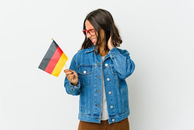 Junge frau, die eine deutsche fahne lokalisiert auf weißer wand hält, die einen nackenschmerz aufgrund von stress, massieren und berühren mit der hand hat