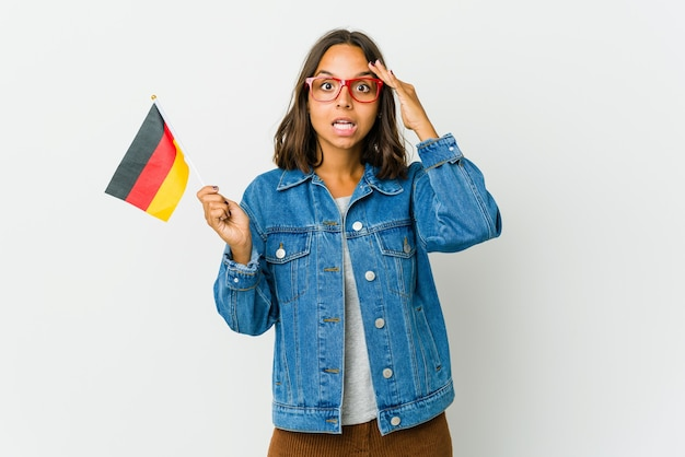 Junge frau, die eine deutsche fahne lokalisiert auf weißer wand hält, schreit laut, hält augen offen und hände angespannt