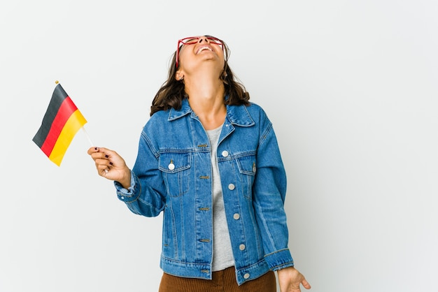 Junge frau, die eine deutsche flagge hält, die auf weißer wand lokalisiert entspannt und glücklich lacht, hals gestreckt zeigt zähne zeigt