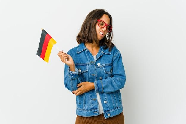 Junge frau, die eine deutsche flagge hält, die ellbogen massiert und nach einer schlechten bewegung leidet