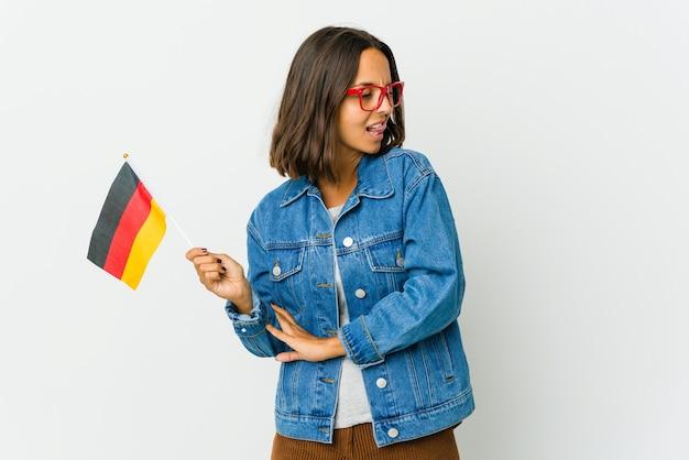 Junge frau, die eine deutsche flagge lokalisiert auf der weißen wand lustig und freundlich herausstehende zunge hält