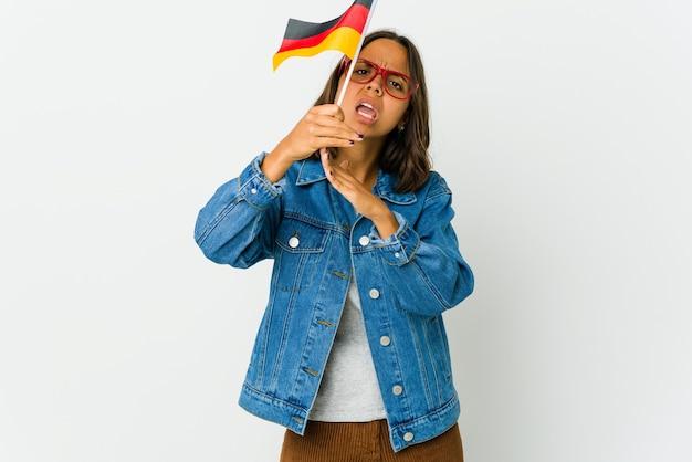 Junge frau, die eine deutsche flagge lokalisiert auf weißer wand hält, die eine zeitüberschreitungsgeste zeigt