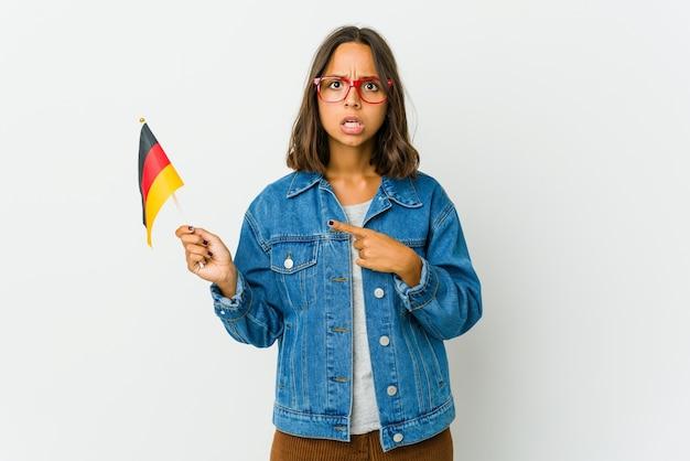 Junge frau, die eine deutsche flagge lokalisiert auf weißer wand hält, die zur seite zeigt