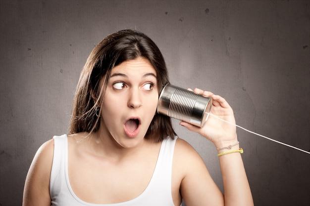 Junge frau, die eine dose als telefon verwendet