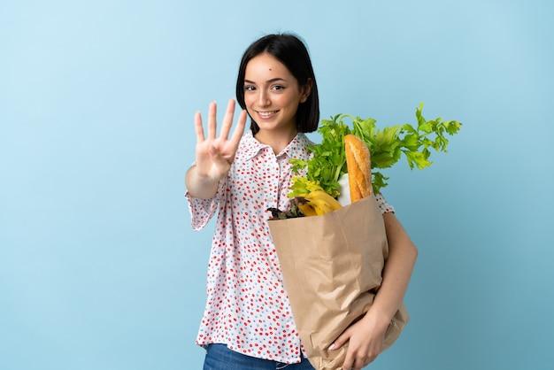 Junge frau, die eine einkaufstasche des lebensmittels glücklich hält und vier mit den fingern zählt