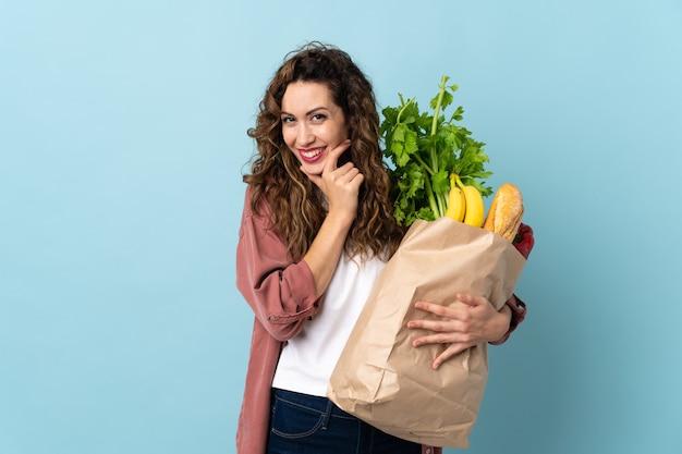 Junge frau, die eine einkaufstasche des lebensmittels lokalisiert auf blauem hintergrund glücklich und lächelnd hält