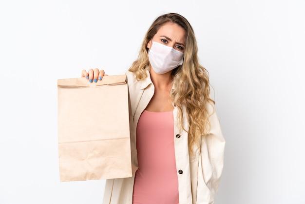 Junge frau, die eine einkaufstasche des lebensmittels lokalisiert auf weiß mit traurigem ausdruck hält