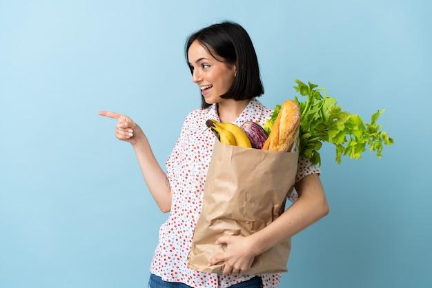 Junge frau, die eine einkaufstüte des lebensmittels hält, zeigt finger zur seite und präsentiert ein produkt