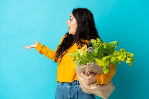 Junge frau, die eine einkaufstüte hält, die auf blauem hintergrund mit überraschungsausdruck isoliert ist, während sie zur seite schaut