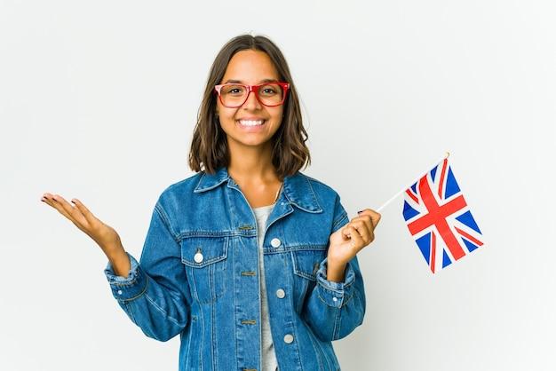 Junge frau, die eine englische flagge lokalisiert auf weißer wand hält, macht skala mit armen, fühlt sich glücklich und zuversichtlich