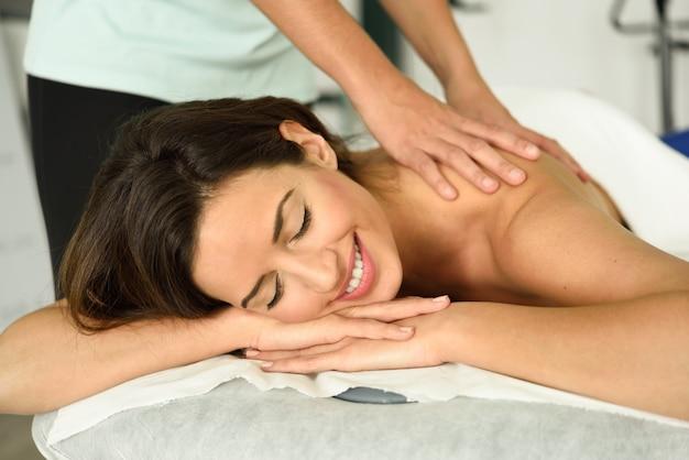 Junge frau, die eine entspannende rückenmassage in einer badekurortmitte empfängt.