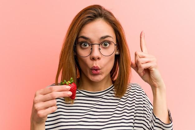 Junge frau, die eine erdbeere hat irgendeine großartige idee, konzept der kreativität hält.