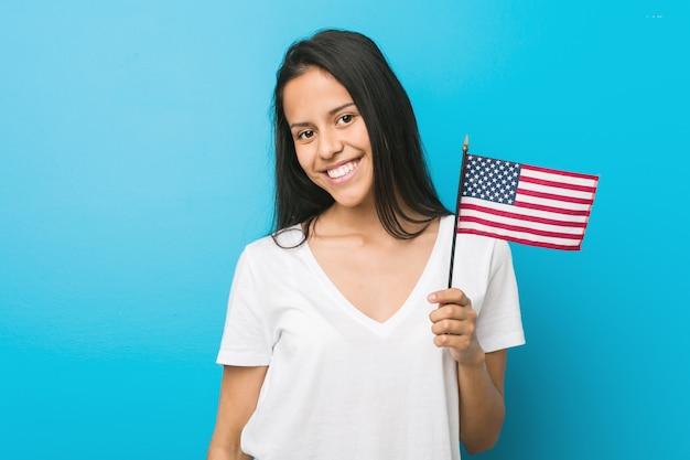 Junge frau, die eine flagge der vereinigten staaten glücklich, lächelnd und fröhlich hält