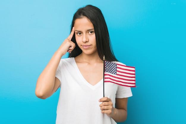 Junge frau, die eine flagge der vereinigten staaten hält, die seine schläfe mit dem finger zeigt, denkend, konzentrierte sich auf eine aufgabe