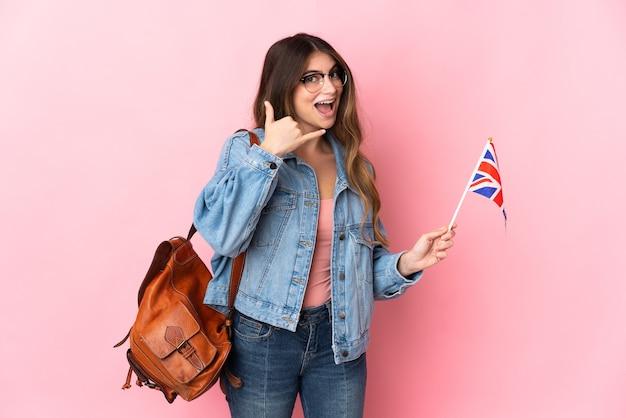 Junge frau, die eine flagge des vereinigten königreichs auf rosa macht, die telefongeste macht.