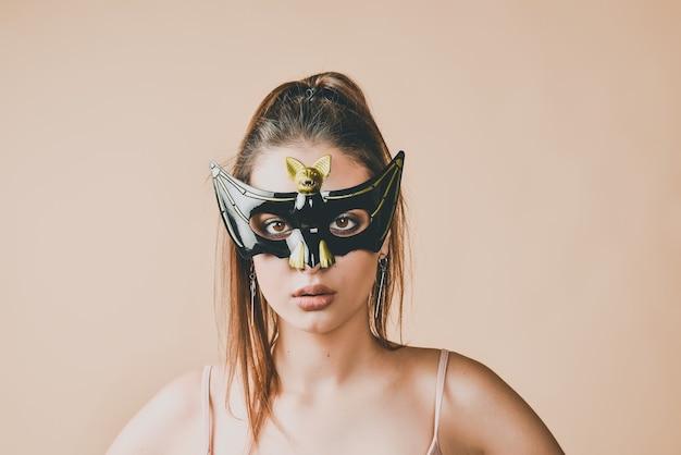 Junge frau, die eine fledermausmaske für maskerade oder halloween-partei trägt.