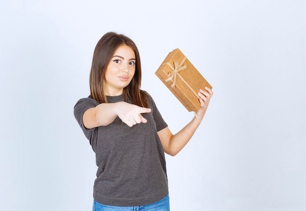 Junge frau, die eine geschenkbox hält und auf die kamera zeigt.