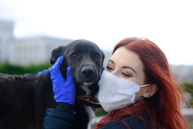 Junge frau, die eine gesichtsmaske als coronavirus-ausbreitungsprävention verwendet, die mit ihrem hund geht. globales covid-19-pandemie-konzeptbild.