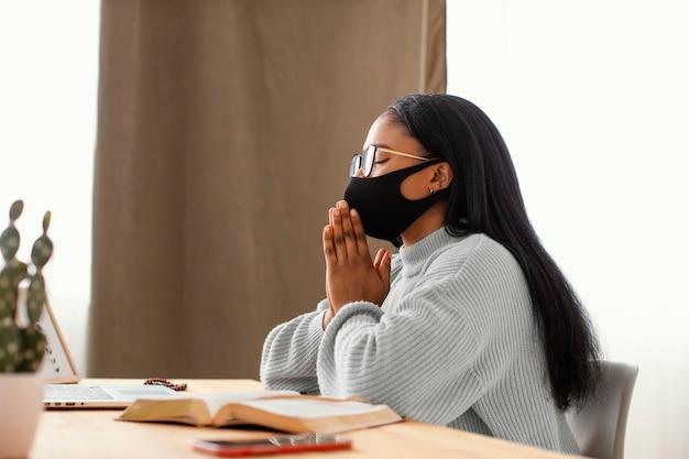 Junge frau, die eine gesichtsmaske beim beten trägt