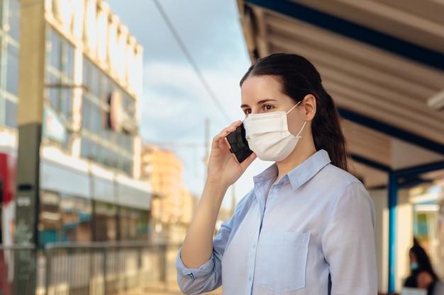 Junge frau, die eine gesichtsmaske trägt und am telefon spricht, während sie auf öffentliche verkehrsmittel wartet.