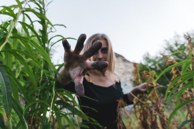 Junge frau, die eine gruselige hexe cosplayt, streckt ihre hand mit schwarzen fingern aus