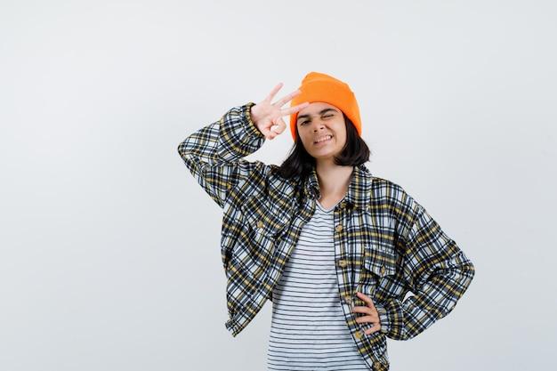 Junge frau, die eine gute geste in einem orangefarbenen, karierten hemd mit hut zeigt, das süß aussieht