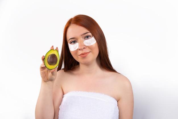 Junge frau, die eine halbe avocado hält. gesundheit, schönheit, spa-konzept.