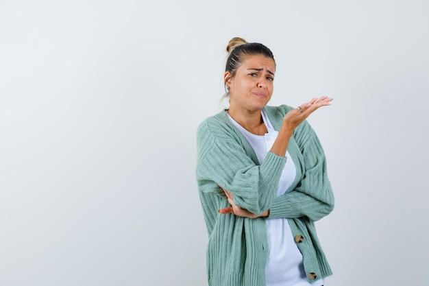 Junge frau, die eine hand am ellbogen hält, während sie eine andere hand in weißem hemd und mintgrüner strickjacke streckt und gehetzt aussieht