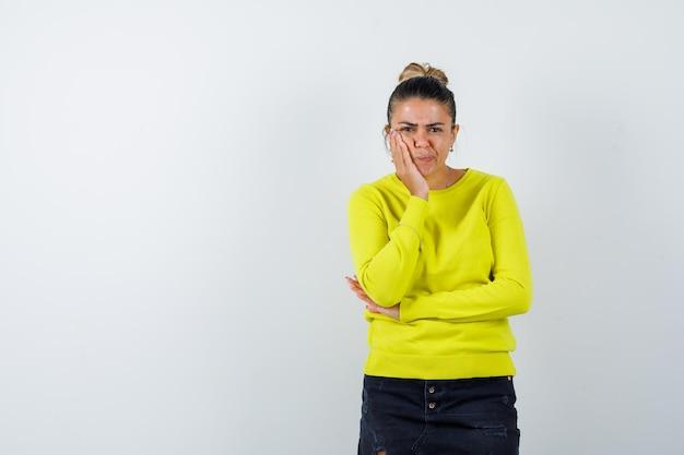 Junge frau, die eine hand auf der wange, eine andere hand auf dem ellbogen in gelbem pullover und schwarzer hose hält und ernst aussieht