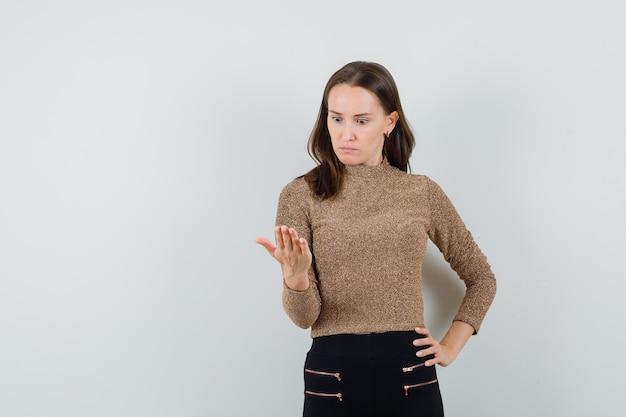 Junge frau, die eine hand auf taille legt und eine andere hand als telefon in golden vergoldetem pullover und in schwarzen hosen hält und überrascht aussieht. vorderansicht.