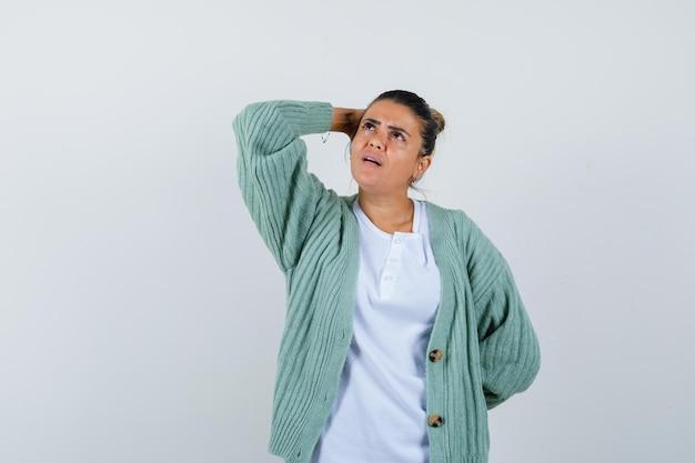 Junge frau, die eine hand hinter dem kopf, eine andere hand hinter der taille in weißem hemd und mintgrüner strickjacke hält und nachdenklich aussieht