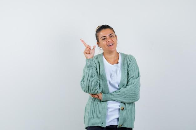 Junge frau, die eine hand in heureka-geste hebt, während sie die hand am ellbogen in weißem t-shirt und mintgrüner strickjacke hält und glücklich aussieht looking