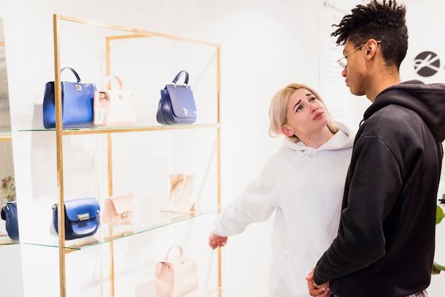 Junge frau, die eine handtasche auf regal zeigt, das sie vom freund kaufen möchte