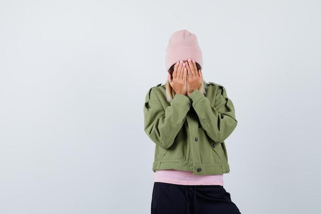 Junge frau, die eine jacke und einen rosa hut trägt, der ihr gesicht bedeckt