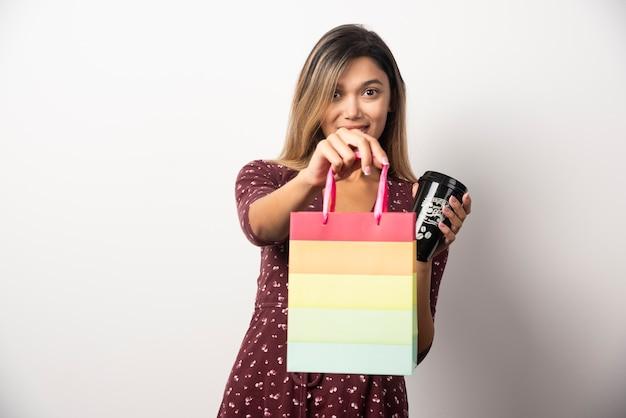 Junge frau, die eine kleine geschäftstasche und eine tasse getränk auf weißer wand hält.