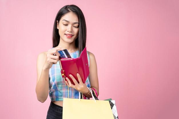 Junge frau, die eine kreditkarte von ihrem geldbeutel mit lächeln auswählt und einkaufstaschen trägt,