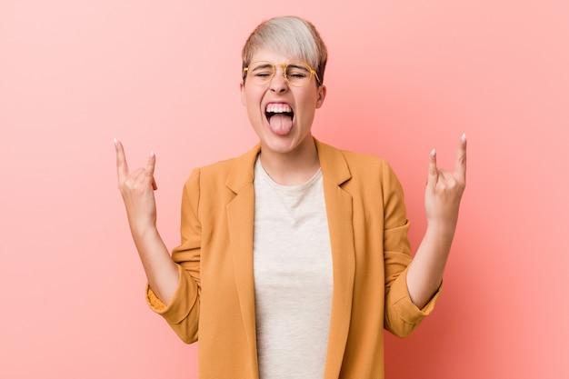 Junge frau, die eine lässige geschäftskleidung trägt, die felsengeste mit den fingern zeigt