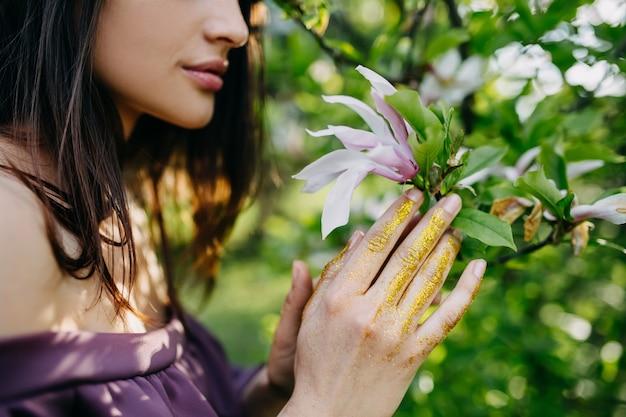 Junge frau, die eine magnolienblume in einem park hält.