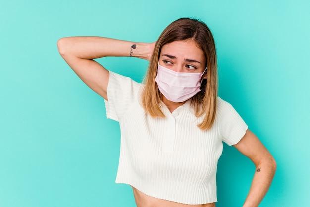 Junge frau, die eine maske für virus lokalisiert auf blauer wand trägt, die hinterkopf berührt, denkt und eine wahl trifft.