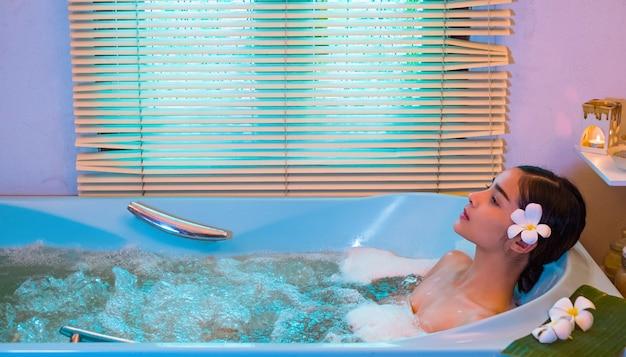 Junge frau, die eine massage, einen badekurort und eine schönheit genießt.